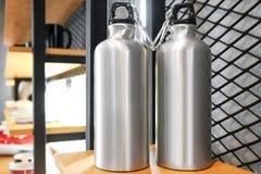 Tazza d'acciaio sullo scaffale bianco Chiavetta inossidabile in bianco per la vostra progettazione Bottiglia isolata per tenere l fotografie stock