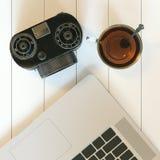 Tazza d'annata della macchina fotografica e del computer portatile e di vetro di tè caldo su duro bianco Immagini Stock Libere da Diritti