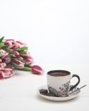 Tazza da caffè su fondo e sui tulipani bianchi Fotografie Stock