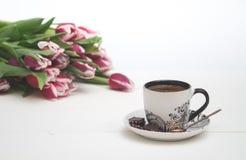 Tazza da caffè su fondo e sui tulipani bianchi Immagini Stock Libere da Diritti