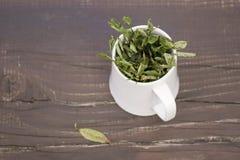 Tazza da the con le foglie secche del mirtillo immagine stock