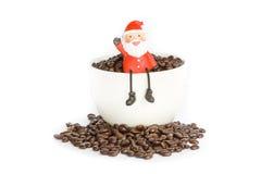 Tazza dei chicchi di caffè del Babbo Natale Fotografia Stock