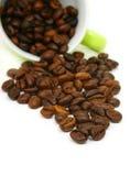 Tazza dei chicchi di caffè su priorità bassa bianca immagini stock