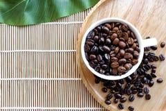 Tazza dei chicchi di caffè sulla vista superiore di legno immagine stock
