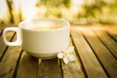 Tazza dei fiori bianchi & del tè sulla tavola di legno con bokeh brillante Fotografia Stock