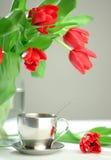 Tazza dei tulipani di colore rosso e del tè Fotografia Stock