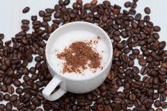 Tazza del caffè del cappuccino con i fagioli Fotografia Stock