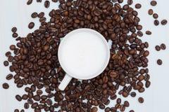 Tazza del caffè del latte con i fagioli Fotografia Stock