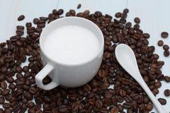 Tazza del caffè del latte con i fagioli Fotografie Stock Libere da Diritti