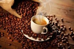 Tazza del caffè espresso con i chicchi della borsa e di caffè della iuta fotografia stock