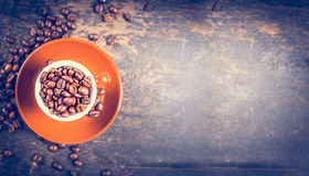 Tazza del caffè espresso in pieno dei chicchi di caffè su fondo di legno rustico, vista superiore Fotografia Stock