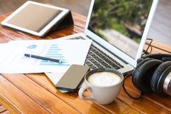 Tazza del computer portatile, della compressa, dello smartphone e di caffè con docume finanziario Fotografia Stock Libera da Diritti