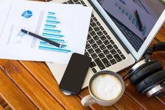 Tazza del computer portatile, della compressa, dello smartphone e di caffè con i documenti finanziari Fotografia Stock