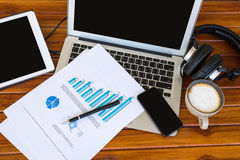 Tazza del computer portatile, della compressa, dello smartphone e di caffè con i documenti finanziari Immagine Stock Libera da Diritti