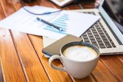 Tazza del computer portatile, della compressa, dello smartphone e di caffè con i documenti finanziari Fotografia Stock Libera da Diritti