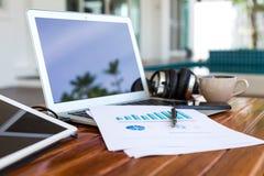 Tazza del computer portatile, della compressa, dello smartphone e di caffè con i documenti finanziari Immagine Stock