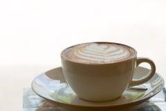 Tazza del latte del caffè di arte su caffè bianco e d'annata con il chiarore leggero caldo Fotografie Stock