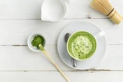 Tazza del latte di matcha del tè verde su fondo bianco da sopra la v piana immagini stock libere da diritti