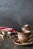 Tazza del tè con le rose dell'anca, camomilla, erbe di autunno sulla tavola di legno Immagine Stock