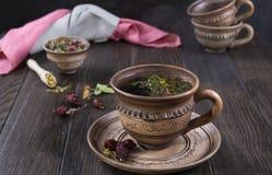 Tazza del tè con le rose dell'anca, camomilla, erbe di autunno sulla tavola di legno fotografia stock