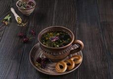 Tazza del tè con le rose dell'anca, camomilla, erbe di autunno sulla tavola di legno Immagine Stock Libera da Diritti