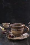 Tazza del tè con le rose dell'anca, camomilla, erbe di autunno sulla tavola di legno Fotografie Stock