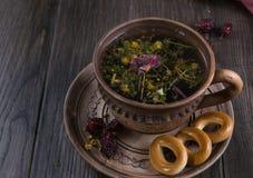 Tazza del tè con le rose dell'anca, camomilla, erbe di autunno sulla tavola di legno fotografia stock libera da diritti