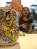 Tazza del tè con un coperchio, con bella pittura asiatica e su una maniglia del dito, stante sulla tavola bianca immagine stock libera da diritti