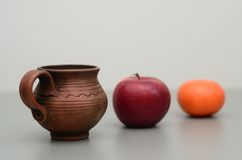 Tazza dell'argilla, mela rossa, mandarino Immagini Stock