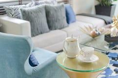 Tazza dell'insieme di tè con la sedia blu di stile classico in salone Fotografia Stock Libera da Diritti