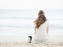 Tazza della bevanda calda vicino alla donna in maglione che si siede sulla spiaggia sola Fotografia Stock Libera da Diritti