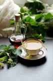 Tazza della porcellana del tè e dello sciroppo d'acero del tiglio su un fondo di legno scuro Fotografia Stock