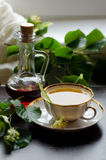 Tazza della porcellana del tè e dello sciroppo d'acero del tiglio su un fondo di legno scuro Immagini Stock