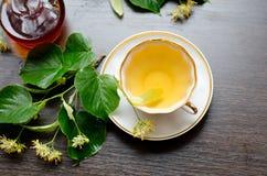 Tazza della porcellana del tè e dello sciroppo d'acero del tiglio su un fondo di legno scuro Immagine Stock