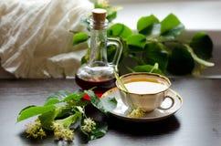 Tazza della porcellana del tè e dello sciroppo d'acero del tiglio su un fondo di legno scuro Fotografie Stock Libere da Diritti