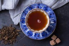 Tazza della porcellana di tè nero su un fondo scuro Bevanda calda - tè nero Fotografie Stock Libere da Diritti