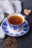 Tazza della porcellana di tè nero su un fondo scuro Bevanda calda - tè nero Fotografia Stock Libera da Diritti