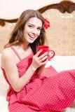 Tazza della tenuta di bella ragazza della bevanda calda in vestito rosso divertendosi rilassandosi a letto macchina fotografica s fotografia stock libera da diritti