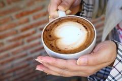 Tazza della tenuta della donna del caffè caldo della moca in sua mano nel caffè durante la stagione invernale immagine stock