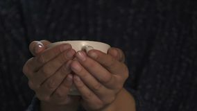 Tazza della tenuta della donna di tè caldo, volontario che la avvolge in coperta, concetto di carità archivi video