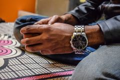 Tazza della tenuta della mano ed indossare un orologio attraente nel polso fotografia stock