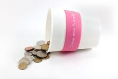 Tazza delle monete che si rovesciano fuori Fotografia Stock