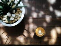 Tazza di bella arte del latte su vecchio fondo di legno Vista superiore fotografia stock libera da diritti