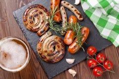 Tazza di birra e salsiccie arrostite Fotografie Stock