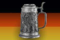 Tazza di birra sui precedenti della bandiera della Germania Fotografie Stock Libere da Diritti