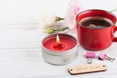 Tazza di caffè, accesa candela rossa, fiori Fotografia Stock