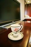 Tazza di caffè al lato della TV Fotografie Stock