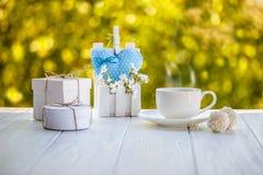 Tazza di caffè all'aperto con il sole delle palle della caramella della noce di cocco su un whi Immagini Stock