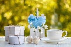 Tazza di caffè all'aperto con il sole delle palle della caramella della noce di cocco su un whi Fotografia Stock