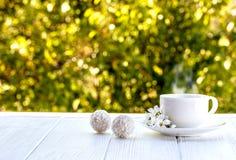 Tazza di caffè all'aperto con il sole delle palle della caramella della noce di cocco su un whi Immagini Stock Libere da Diritti
